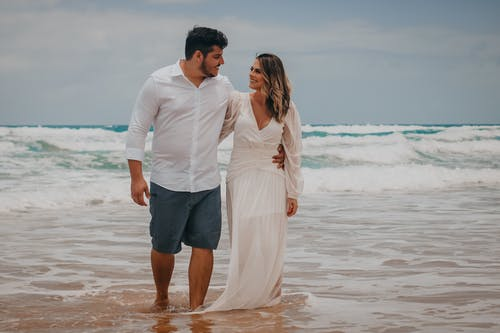 Full length of happy couple in stylish outfits hugging and walking along sandy coast against ocean with waves under cloudy sky in daytime
