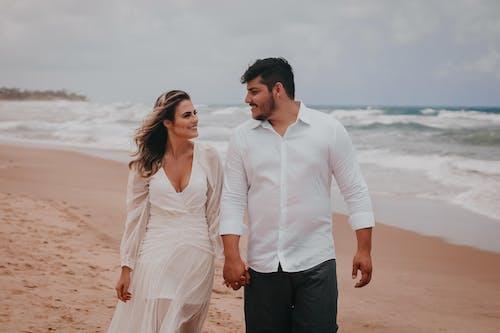 Romantic couple walking on sandy coast of ocean