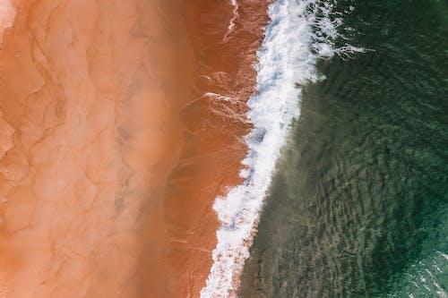 Ocean foamy water rolling on sandy shore