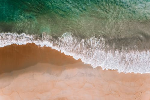Drone view of green ocean water rolling over sandy beach