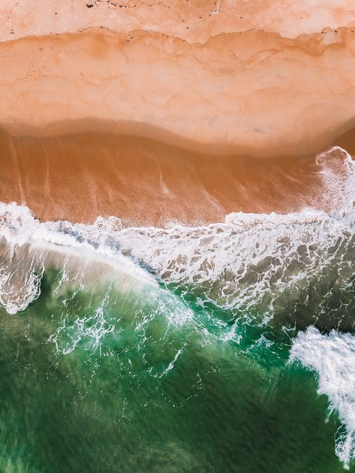 Aerial top view of foamy sea waves with clean green water rolling over wet coast with red sand on fair weather
