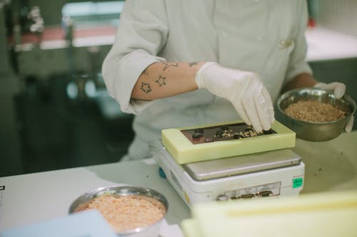 Person in White Chef Uniform Holding White and Green Plastic Container