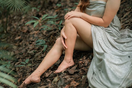 Crop sensual woman with crumpled textile resting on hill