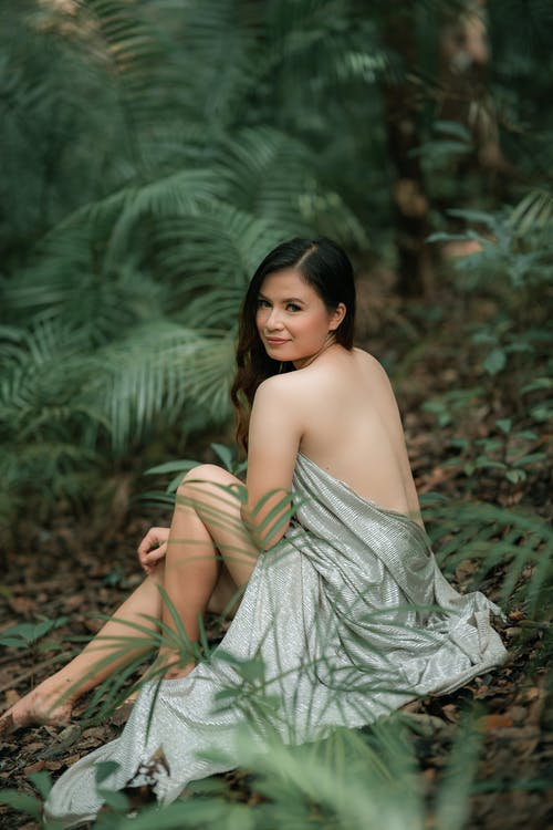 Back view of young sensual ethnic female wrapped in drapery with makeup looking at camera while resting among fern plants