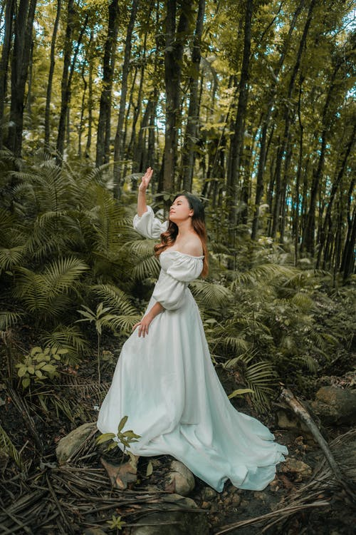 Stylish dreamy woman in white dress in forest