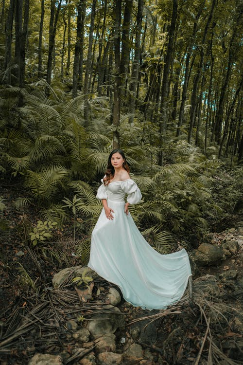 From above of young woman in stylish bridal dress standing with hand on hip in forest while looking at camera