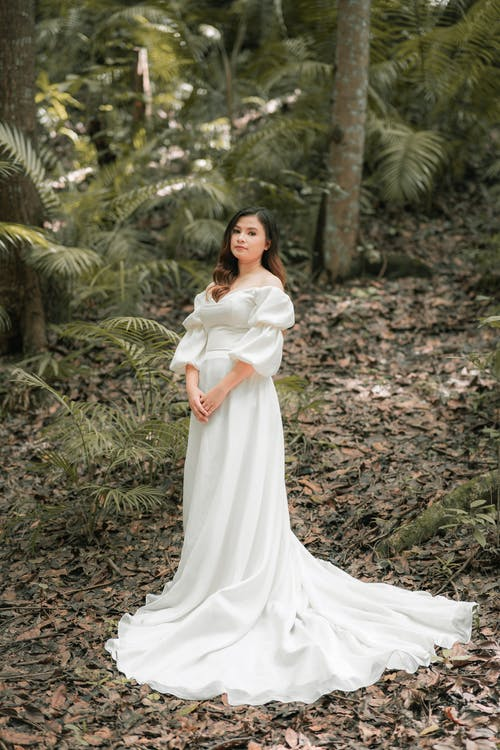 Asian bride in white dress in park on wedding day
