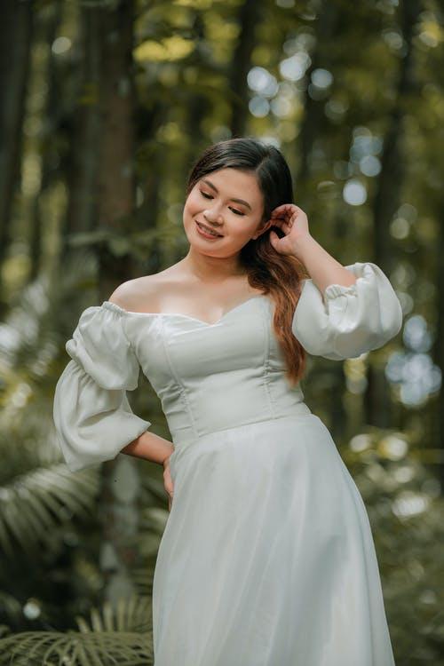 Young happy ethnic woman in elegant bridal dress with makeup touching hair in woods on wedding day