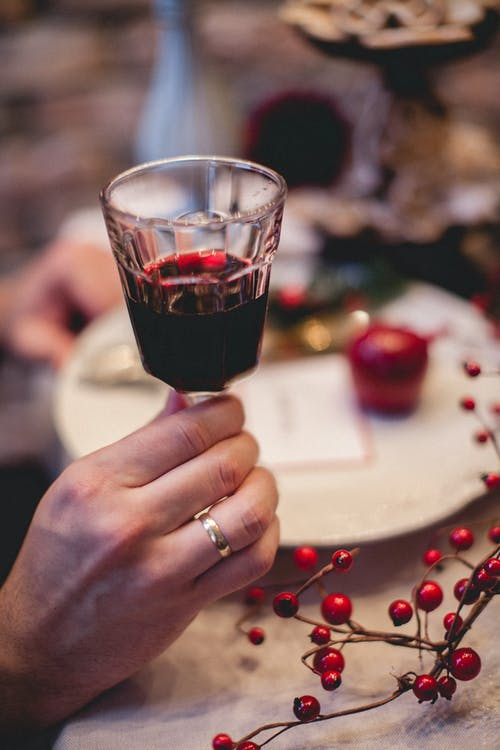 Person Holding Clear Drinking Glass With Red Wine
