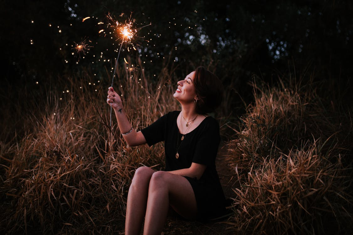 Woman Holding Sparkler While Sitting Down