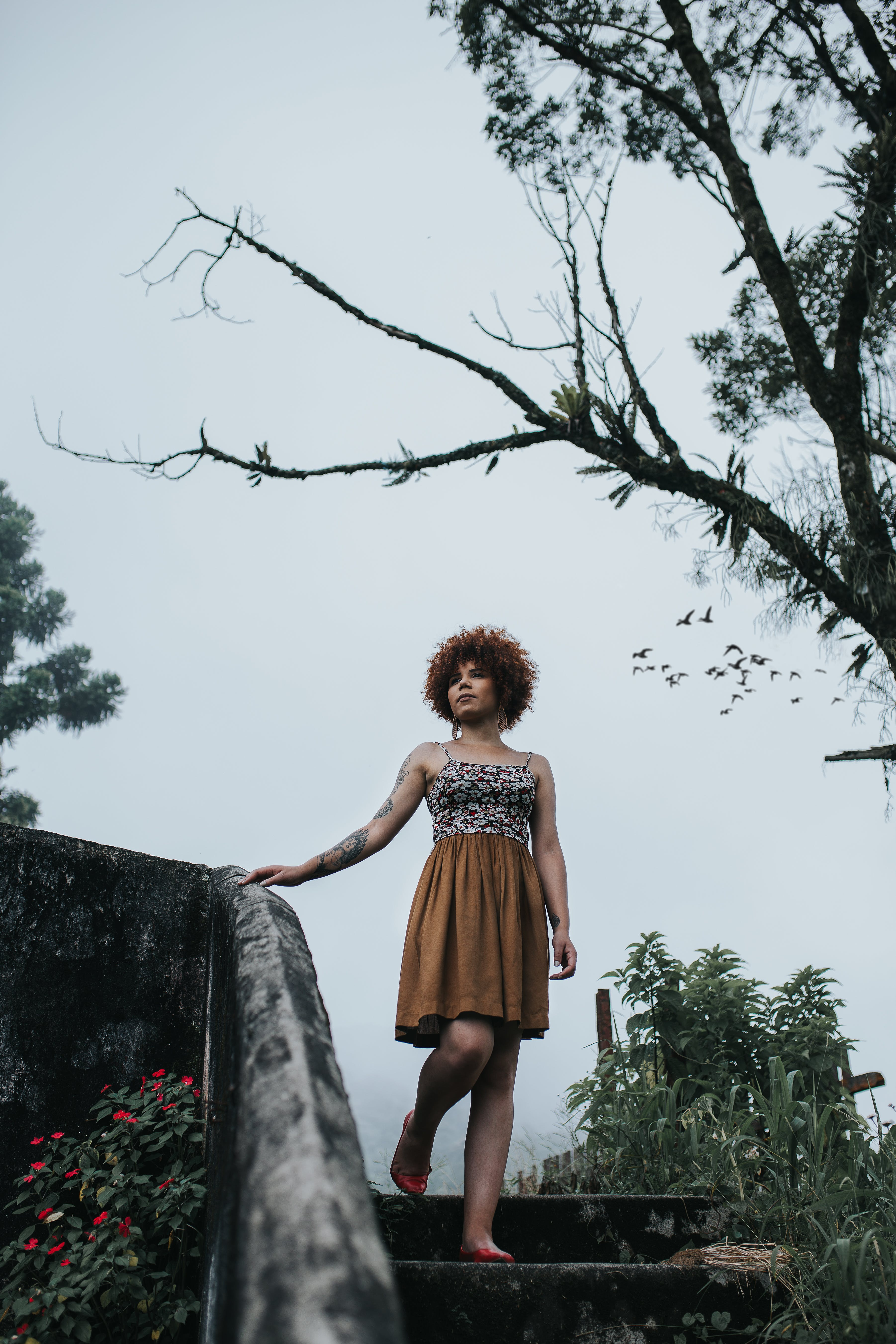 Woman Wearing Red and Black Spaghetti Strap Dress Holding Concrete Railings Under Bare Tree