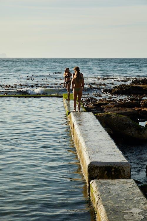 Women Wearing Swimsuits Standing on a Platform Beside the Sea