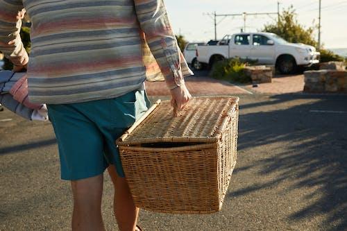 Persona En Pantalones Cortos De Mezclilla Azul Con Cesta Tejida Marrón