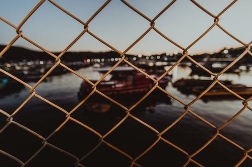 Through metal mesh fence of city port against evening sky