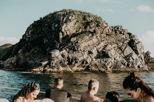 Anonymous tourists in cruise ship sailing near rocky cliff