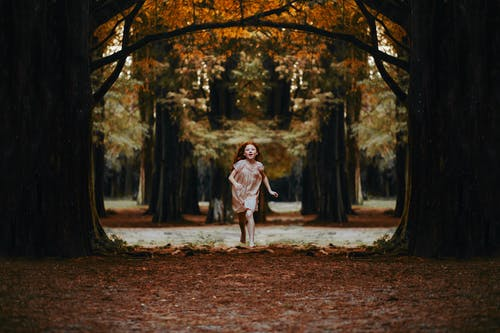 Girl Running Between Trees