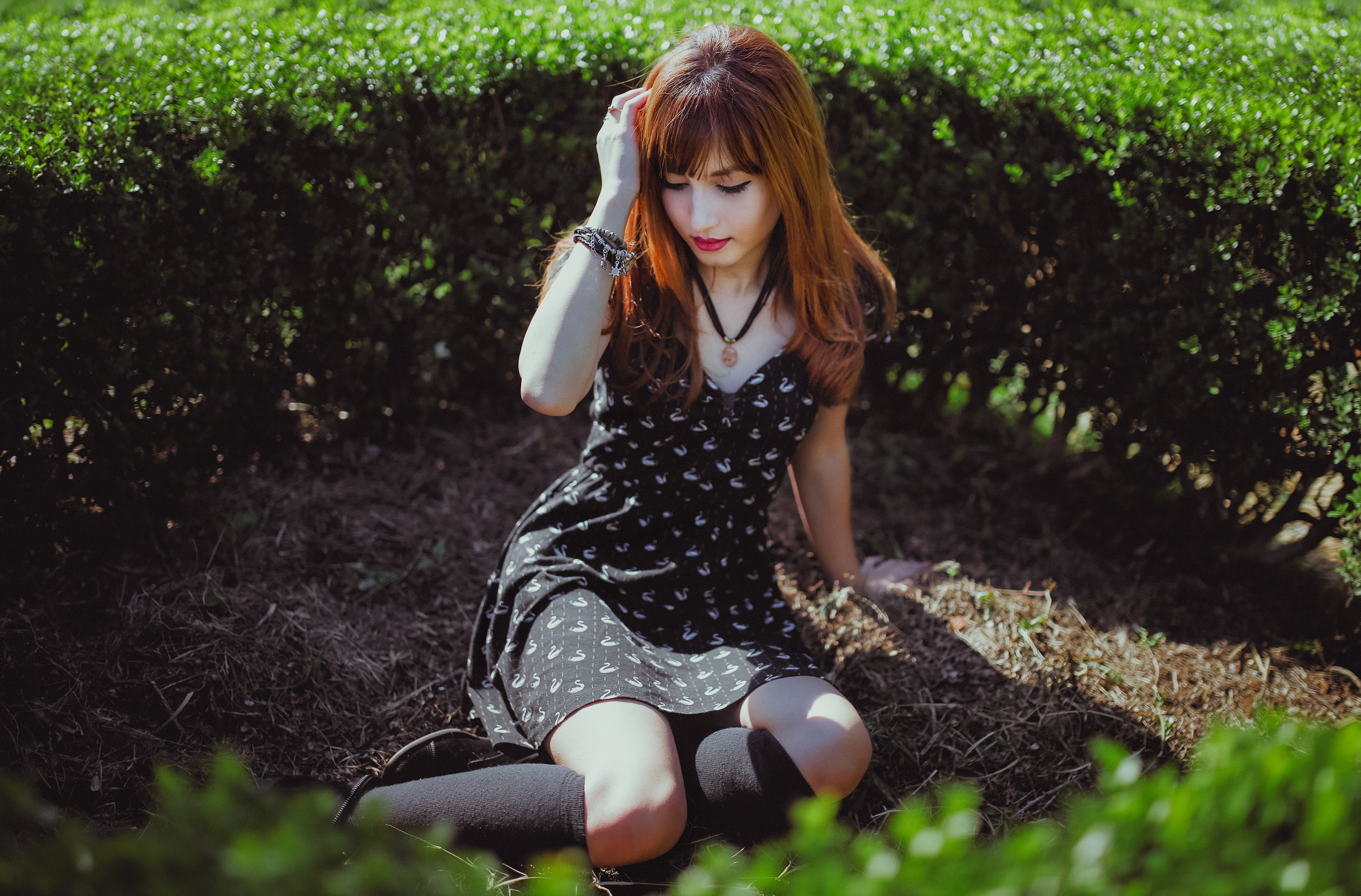 Woman Sitting on the Ground Beside Bushes