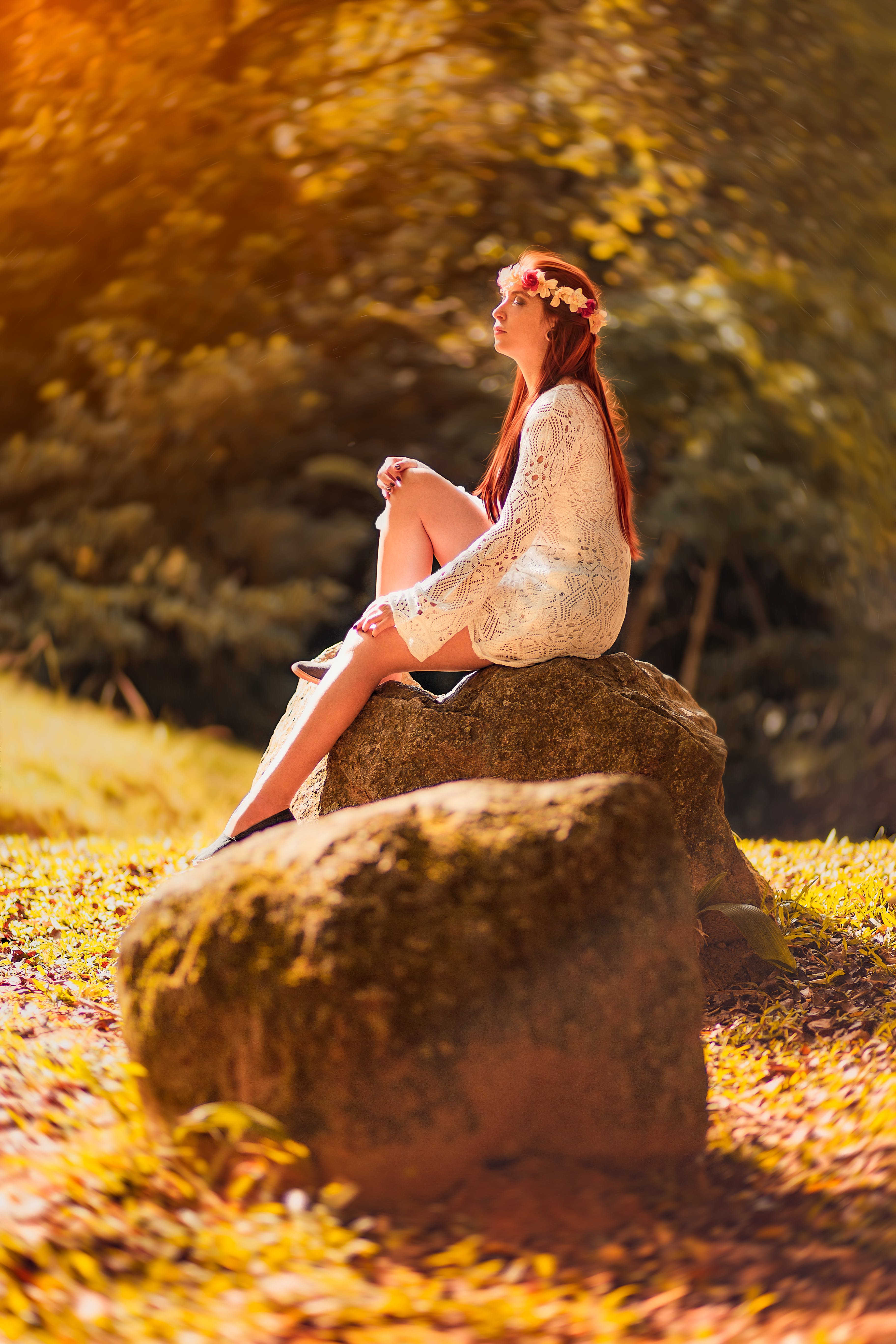 Woman Sitting on Brown Stone