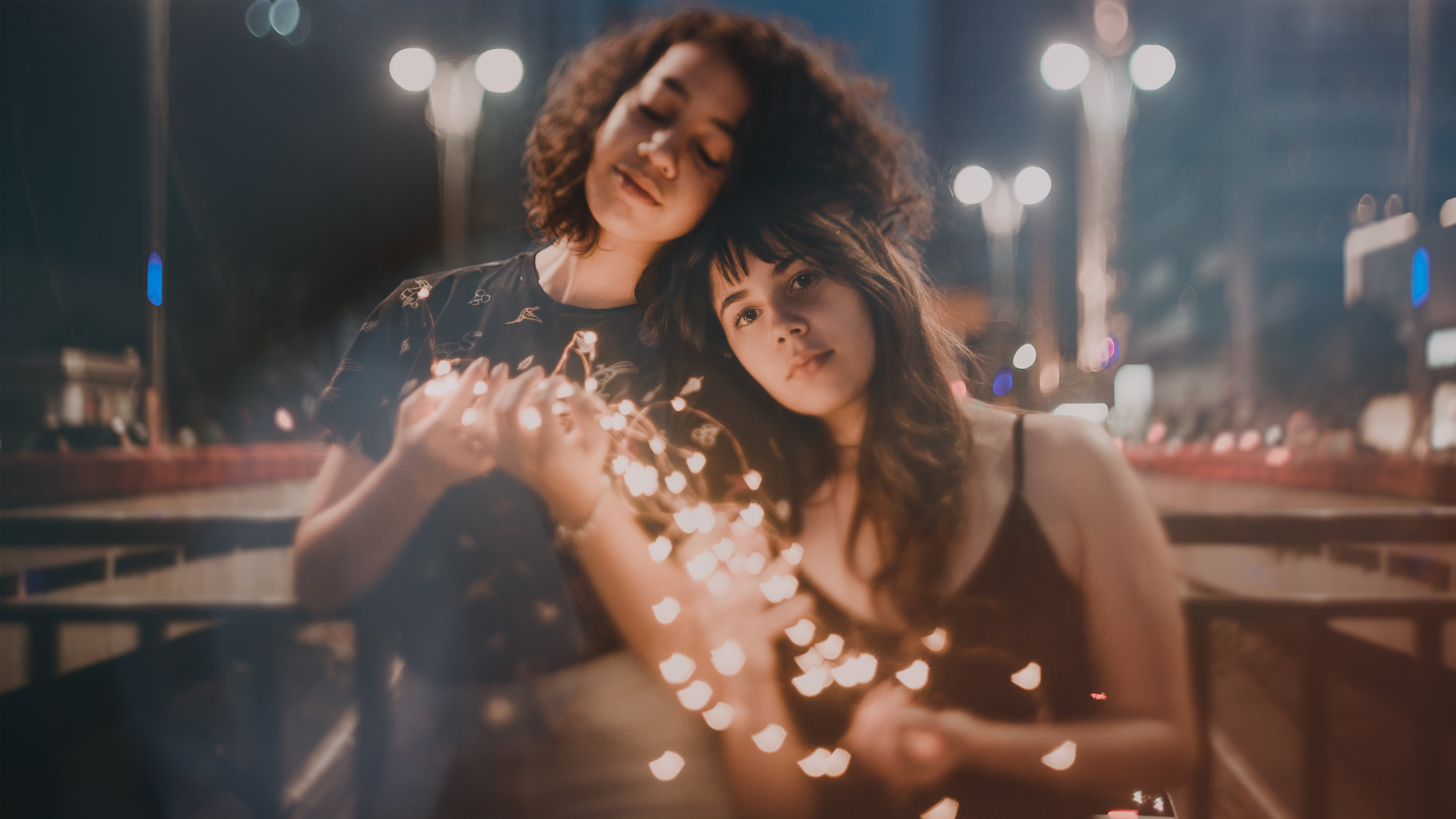 Selective Focus Photography of Two Women Holding String Lights Turned on