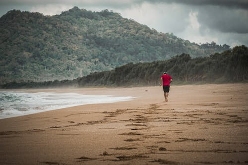 Person in Red Jacket Walking on Beach