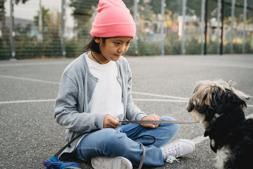 Attentive ethnic kid in casual wear sitting with crossed legs near cute dog in town