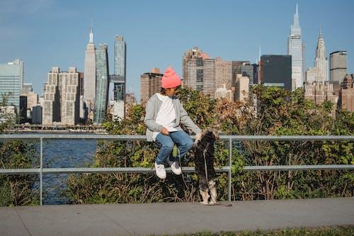 Little boy stroking dog on embankment