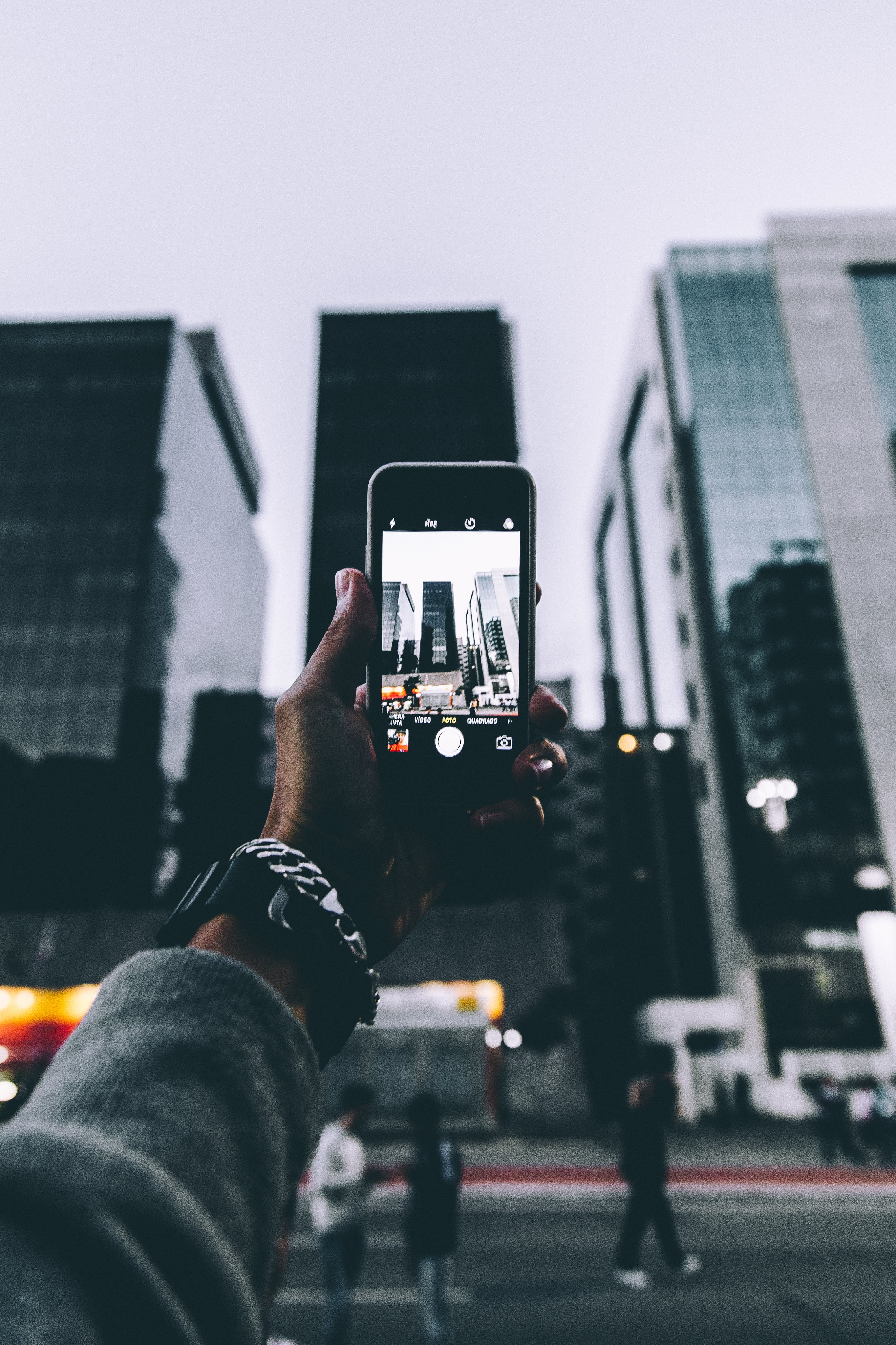 Person Taking Photo of High Rise Building