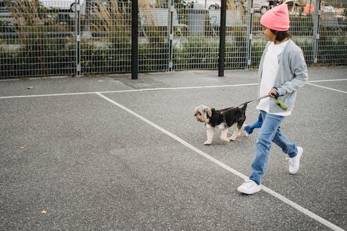 Happy ethnic boy walking with dog