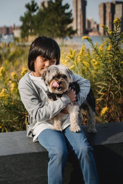 Ethnic child cuddling puppy while sitting on stone border in park with lush vegetation