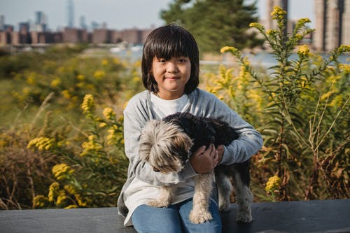 Happy little boy with modern haircut hugging fluffy dog while relaxing in park and looking at camera