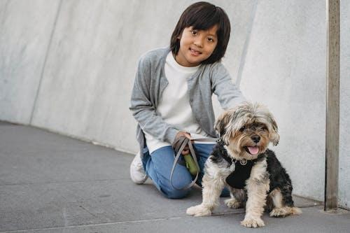 Cheerful Asian boy with fluffy dog