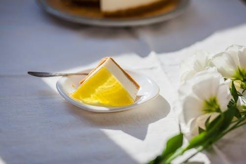 Tasty cheesecake near decorative flowers on table