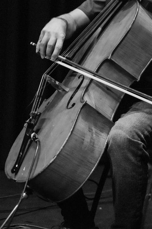Black and white of crop anonymous male musician playing violoncello with bow while sitting on black background