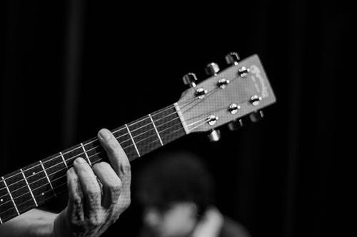 Black and white of crop anonymous male guitarist playing guitar against partner during musical performance on black background