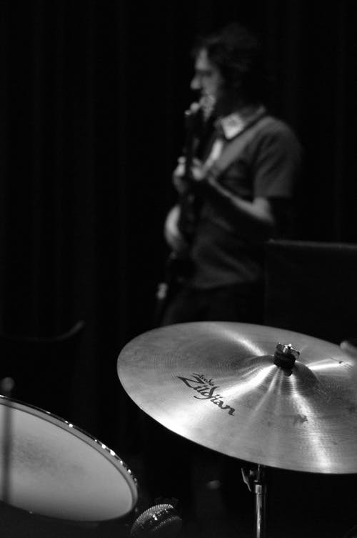 Black and white side view of male musician playing guitar against drum and cymbals during musical performance on black background