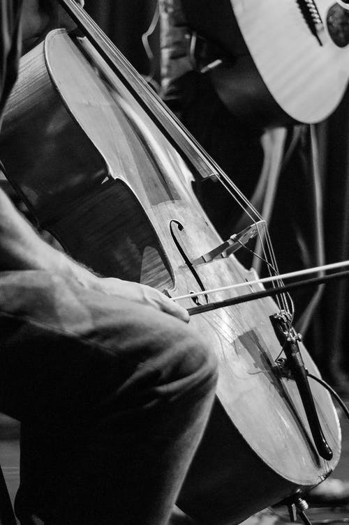 Black and white of crop unrecognizable male cellist playing violoncello against partner with classical guitar during musical performance
