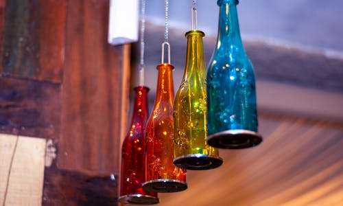 Decorative creative lamps made of bright colorful glass bottles hanging under ceiling in light room