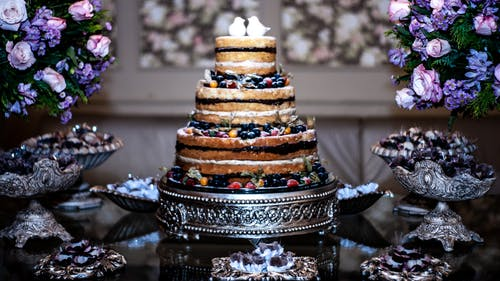 Wedding layer cake garnished with berries and served on glass table near sweets and aromatic blue bouquets in banquet hall