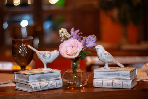 Souvenirs representing sparrows on stacked books placed on wooden table near flowers in vase