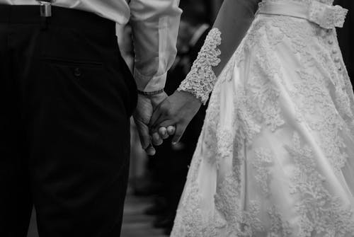 Black and white faceless elegant bride and groom holding hands gently while standing in wedding hall