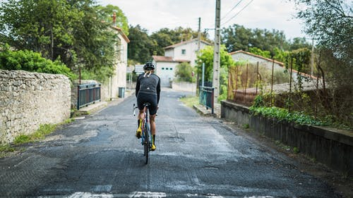 Person in Black Long Sleeve Shirt Riding Bicycle on the Road