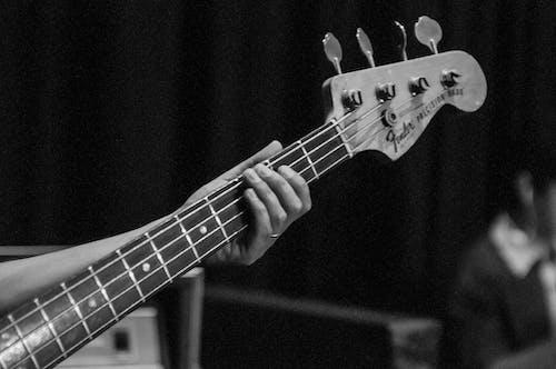Crop unrecognizable guitarist holding guitar neck
