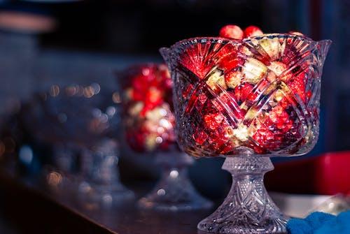 Delicious sweet wild strawberries served in glass dessert bowls on shelf in dark room