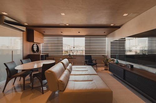 Stylish interior design of contemporary spacious living room with cozy leather sofa and dining table