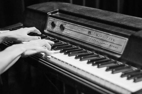 Black and white of crop anonymous person musician playing retro electro piano in room