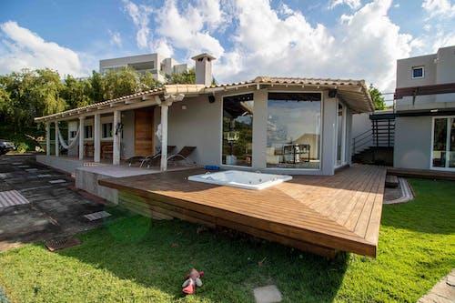 Hydro massage bath on veranda of villa with deckchairs and hammock hanging near wooden benches