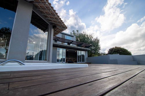 Low angle of board floor on veranda of mansion with transparent glass walls at resort