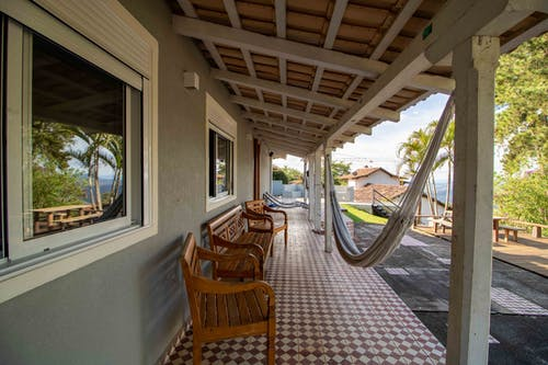 Row of wooden benches placed on tiled floor on veranda of villa located in tropical resort