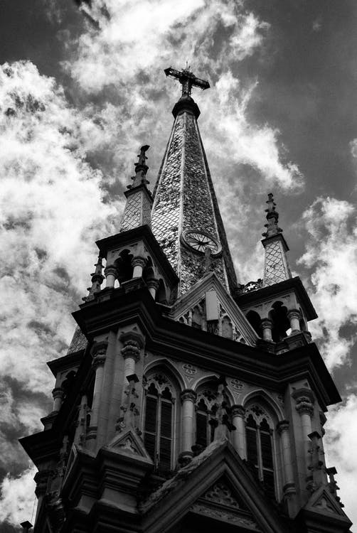 Black and white low angle facade of Catholic cathedral with carved details and arched windows