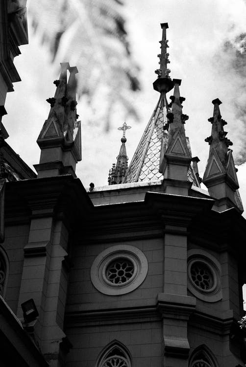Old cathedral with cross and spires on roof